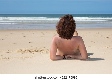 woman nude sitting from the back on beach