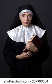 woman in nun veil with book over grey background