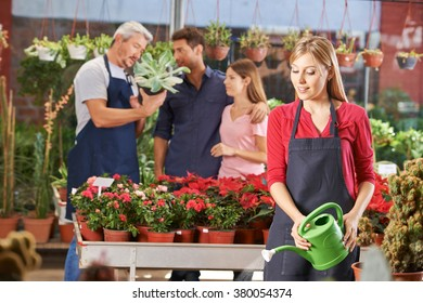 Woman in nursery shop watering plants and flowers with watering can
