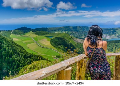 "Woman observes the beautiful view of Lake Sete Cidades ""Lagoa das Sete Cidades"" in Sao Miguel, Azores, Portugal"