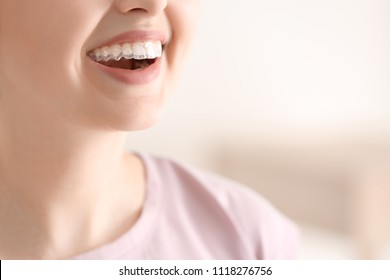 Woman with occlusal splint on light background, closeup