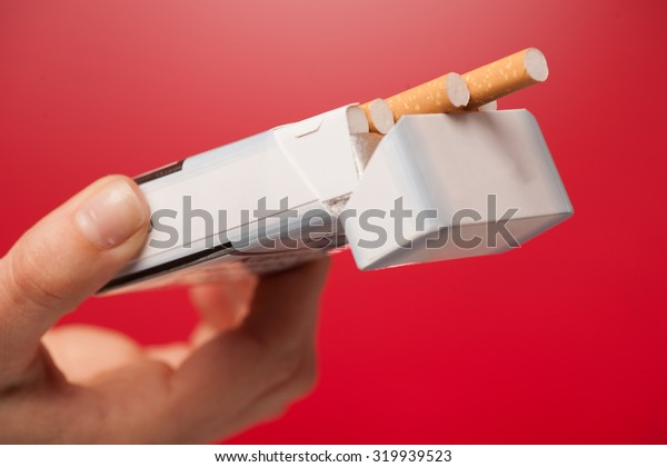 woman offering a cigarette over red background