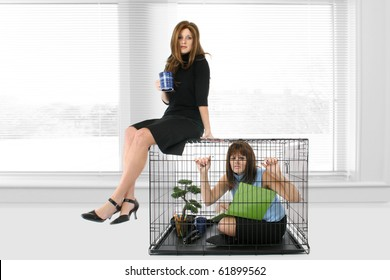 Woman at office in cage looking stressed while woman takes coffee break on top of cage.
