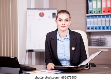 Woman in office with a chart folder in hands. Finance and business