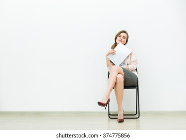 woman in office outfit sitting in a chair with some sheets of paper in hand and thinking