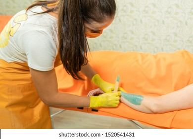 a woman in the office is preparing to remove wax on her hands with wax. the master bent over a woman lying on an orange couch. the client in the office is under an orange blanket