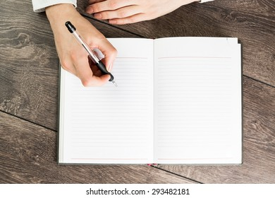 A woman office worker hands writing on empty(blank) book(note, diary) spread(unfold) mockup, top view, studio. Empty space in a notebook for blog entries, you can place your text or information.