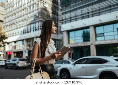 Woman office worker holding a tablet computer in their hands, looking for something in the city