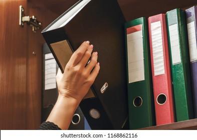 a woman officer pick a binder of document on the row of file folders and paper that nicely management system on the office's shelves and holing it with her hand