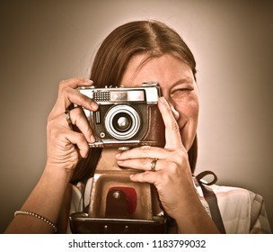 Woman with old camera isolated on grey background