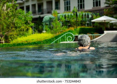 Woman, old woman, old man, swimming in the pool The middle of nature and the morning sun. Rear view of an old woman
