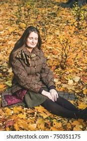 Woman on autumn leaves carpet