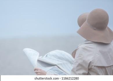 Woman on autumn lonlely beach reading newspaper