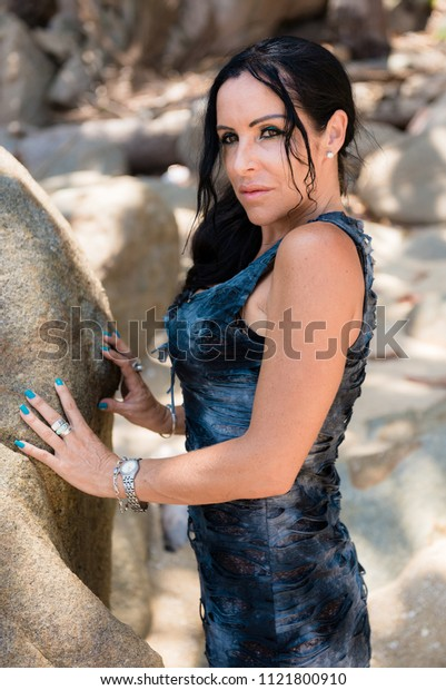 woman on the background of natural stones photographed on a bright Sunny day