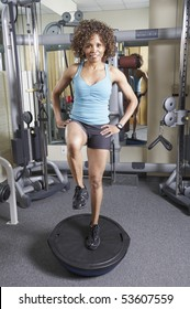 Woman on a balance trainer exercising in the gym