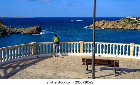 woman on balcony on Arenal d'en Castell beach, Menorca, Balearic Islands, Spain