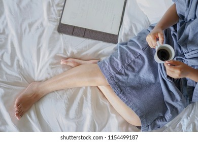 Woman on a bathrobe and morning coffee in bed , Relax with the holidays concept.