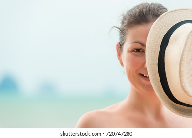 woman on the beach covers half of her face with a hat