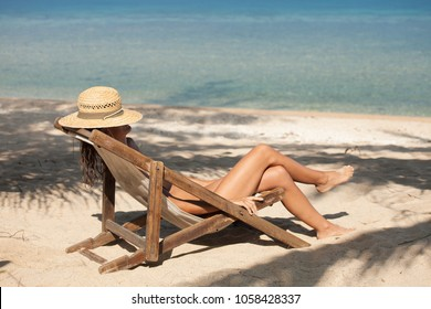 woman on the beach in a deck chair in summer