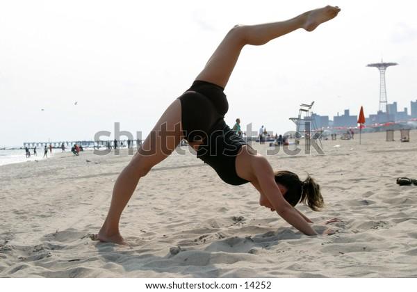 woman on beach doing yoga