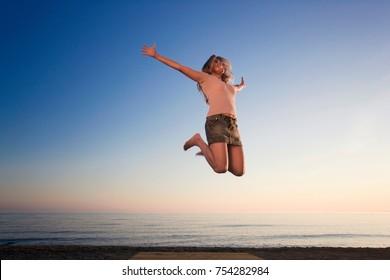 Woman on beach jumping for joy