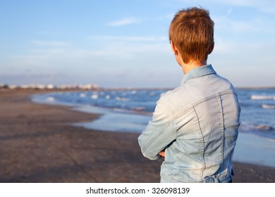 Woman on the beach looking at the horizon .