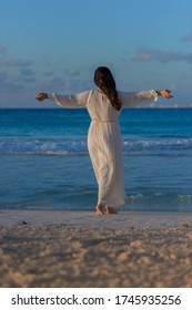 A woman on the beach looks at the horizon and walks along the beach.