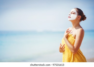 woman on the beach with mask on face