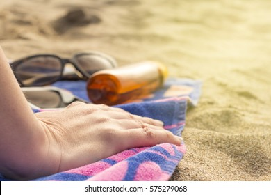 Woman on the beach with protection cream and sunglasses. Close up