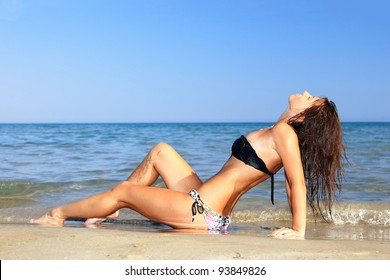 Woman on the beach sitting enjoying the summertime