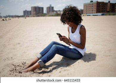 Woman on a beach sitting texting cell phone