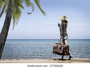 Woman on the beach with vintage leather bag - Travel concept