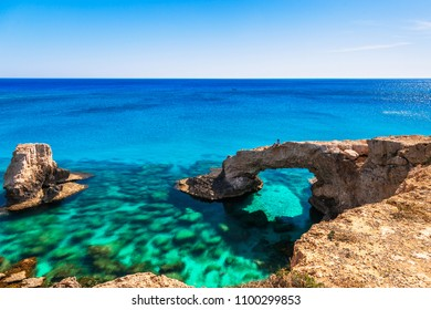 Woman on the beautiful natural rock arch near of Ayia Napa, Cavo Greco and Protaras on Cyprus island, Mediterranean Sea. Legendary bridge lovers. Amazing blue green sea and sunny day.