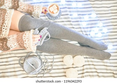 Woman on the bed knits a scarf. Female feet on a bed in socks with a coffee and three marshmallows. Top view