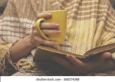Woman on the bed with old book and cup of coffee in hands, top view point. Copy space for text. Soft photo