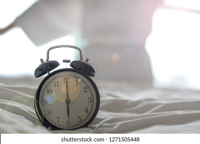 Woman on bed wake up stretching in bedroom with alarm clock at 6.00 a.m. morning. Biological Clock healthcare concept