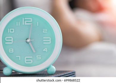 Woman on bed wake up stretching in bedroom with alarm clock at 5.00 a.m. morning. Biological Clock healthcare concept