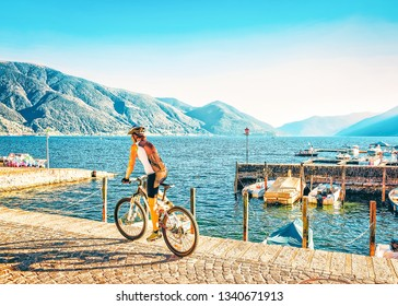 Woman on bicycle at Ascona luxury tourist resort promenade on Lake Maggiore in Ticino canton in Switzerland in summer. People outdoor street travel. Swiss persons expensive holiday and vacation.