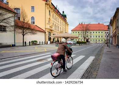 Woman on bicycle at National Hall in the center of Celje old town in Slovenia. Building architecture in Slovenija.