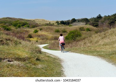 woman on a bike in the dunes of ameland, netherlands