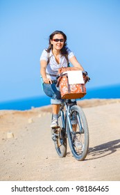 Woman on bike outdoors smiling. Vertical view