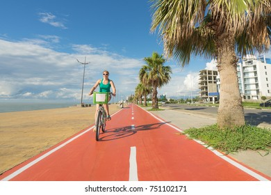 Woman on bike ridding on special bicycle lane on the sea coastline.