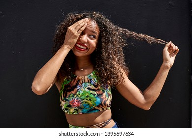 Woman on a black wall covering one eye and pulling her curly hair