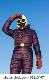Woman on blue sky background in sport ski clothes in goggles.