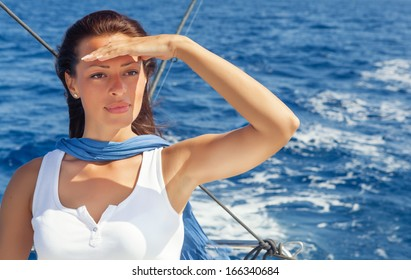 Woman on the bow of a Sailboat enjoying summer sailing and looking away.Copy space