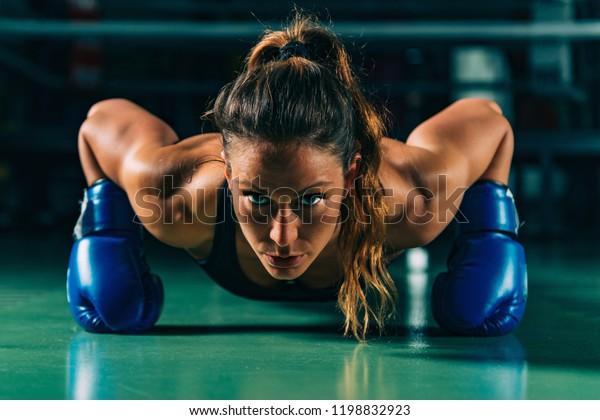 Woman on boxing training doing push ups