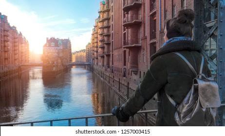 Woman on Bridge across channel in old warehouse district Speicherstadt and enjoying the view. Hamburg. Germany
