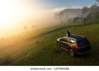 Woman on car travel enjoying freedom.out car sunroof on  travel  on the high mountains with fog covered