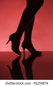 Woman on the catwalk towards red background