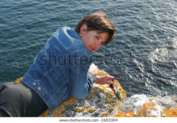 Woman on a cliff  looking at the photographer